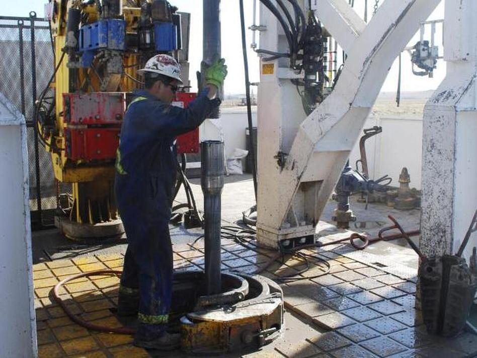 """A worker at Encana's Frenchie Draw gas-drilling rig in central Wyoming guides sections of steel pipe into an 11,000-foot well in 2009. The EPA on Thursday has tied contamination in drinking water to chemicals used in the drilling technique, called hydraulic fracturing, or """"fracking."""""""