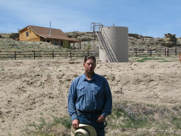This May 2009 picture shows John Fenton, a farmer who lives near Pavillion in central Wyoming, standing near a tank used in natural gas extraction. Fenton and some of his neighbors blame fracking for fouling their well water.