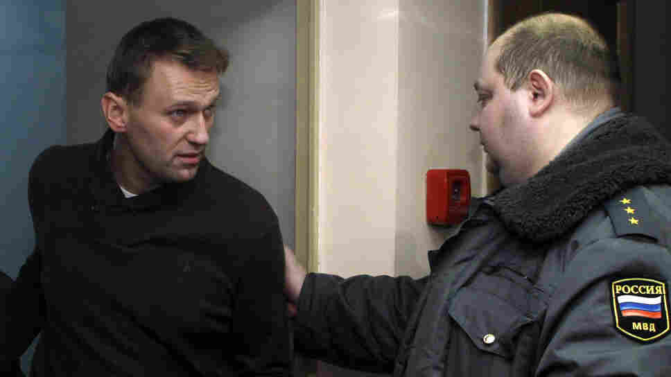 Lawyer and anti-corruption activist Alexei Navalny, left, is taken to court in Moscow on Tuesday. Navalny was detained Monday along with 300 protesters who rallied against what they called vote rigging during Sunday's parliamentary election.