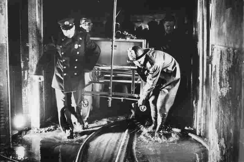 A fireman and other rescue workers carry a hospital bed through a Hartford Hospital corridor, flooded during the fight to extinguish the blaze.