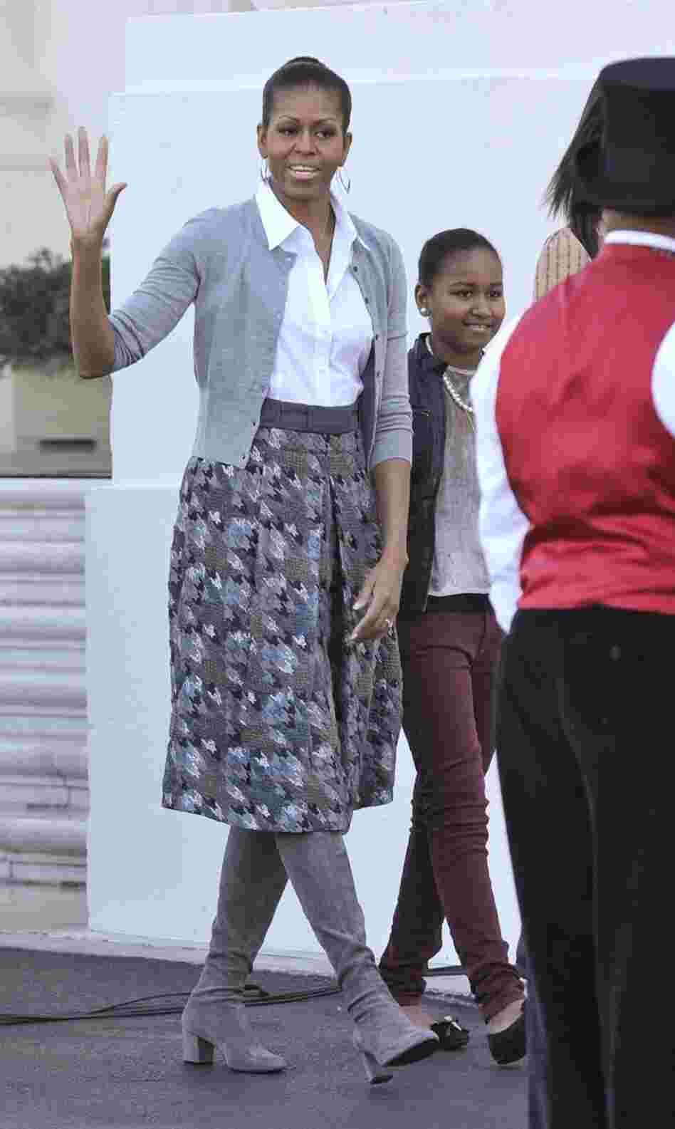 Michelle Obama shows off a gray outfit with a simple cardigan and a houndstooth skirt.