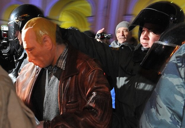 Riot police officers detain a man in a mask depicting Russia's Prime Minister Vladimir Putin during an oppositio