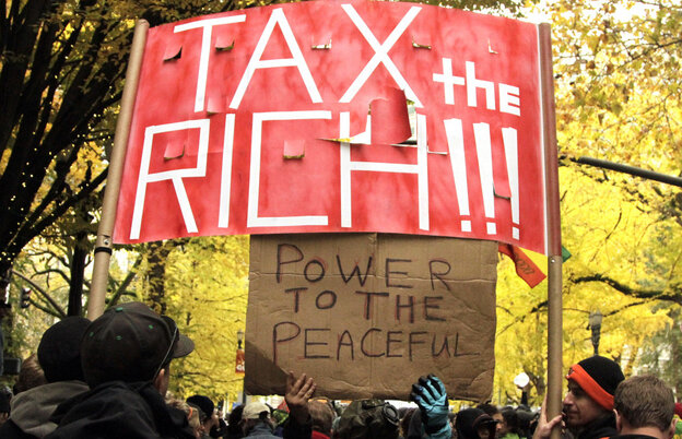 """Protesters fill the street and carry signs across from the Occupy Portland camp in Portland, Ore., holding a sign that demands """"Tax the rich!"""""""