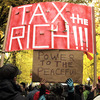 "Protesters fill the street and carry signs across from the Occupy Portland camp in Portland, Ore., holding a sign that demands ""Tax the rich!"""