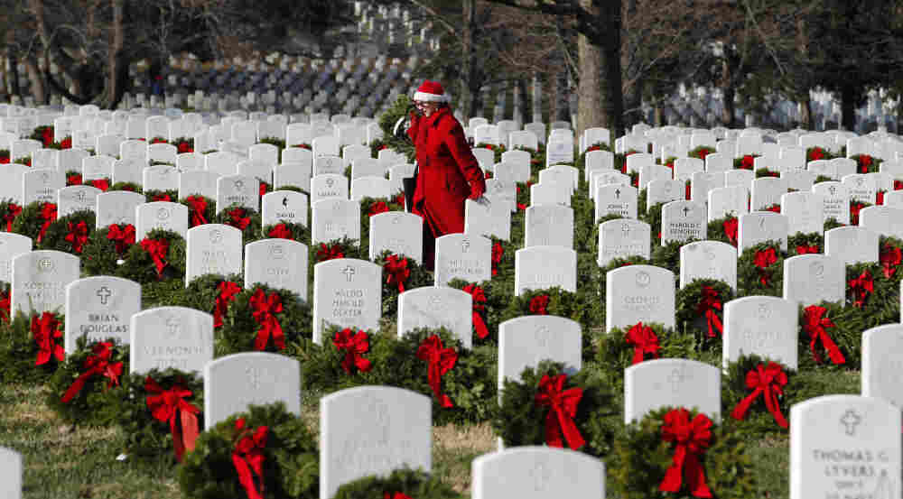 Volunteer Pati Redmond of Frederick, Md., helps to lay holiday wreaths over the graves of fallen soldiers at Arlington National Cemetery in Washington Saturday.