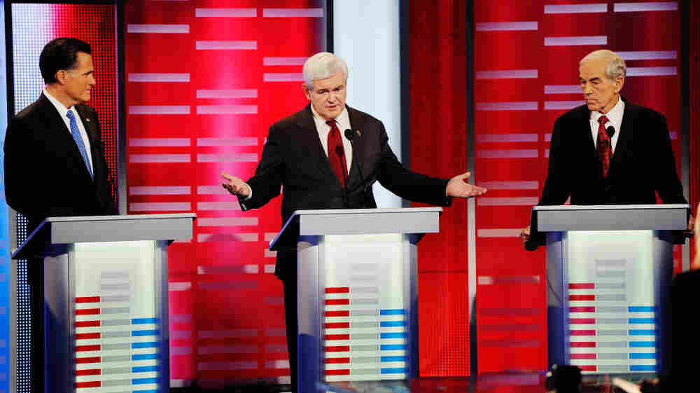 Former House Speaker Newt Gingrich speaks while former Massachusetts Gov. Mitt Romney and U.S. Rep. Ron Paul look on during the ABC News GOP presidential debate on Saturday in Des Moines, Iowa.