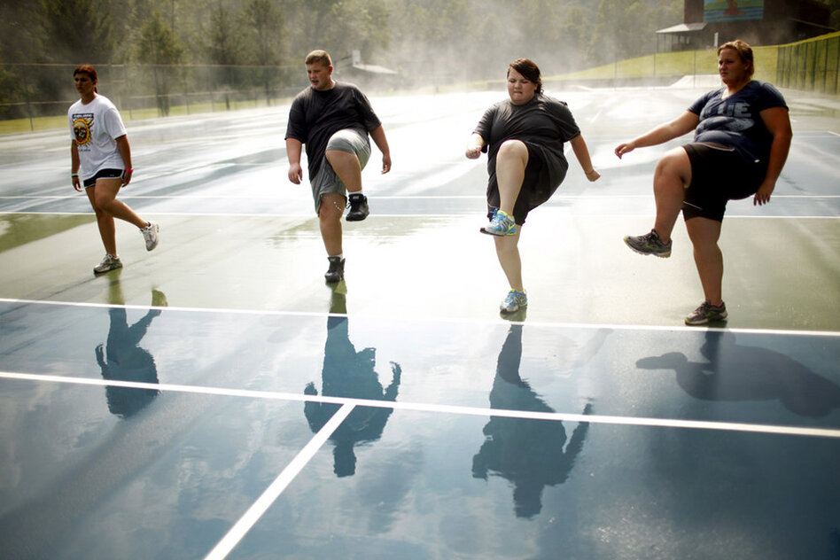 Students do high steps on the tennis court. Exercise is paramount at Wellspring, and a little rain doesn't get in the way of outdoor activities. (Travis Dove for NPR)