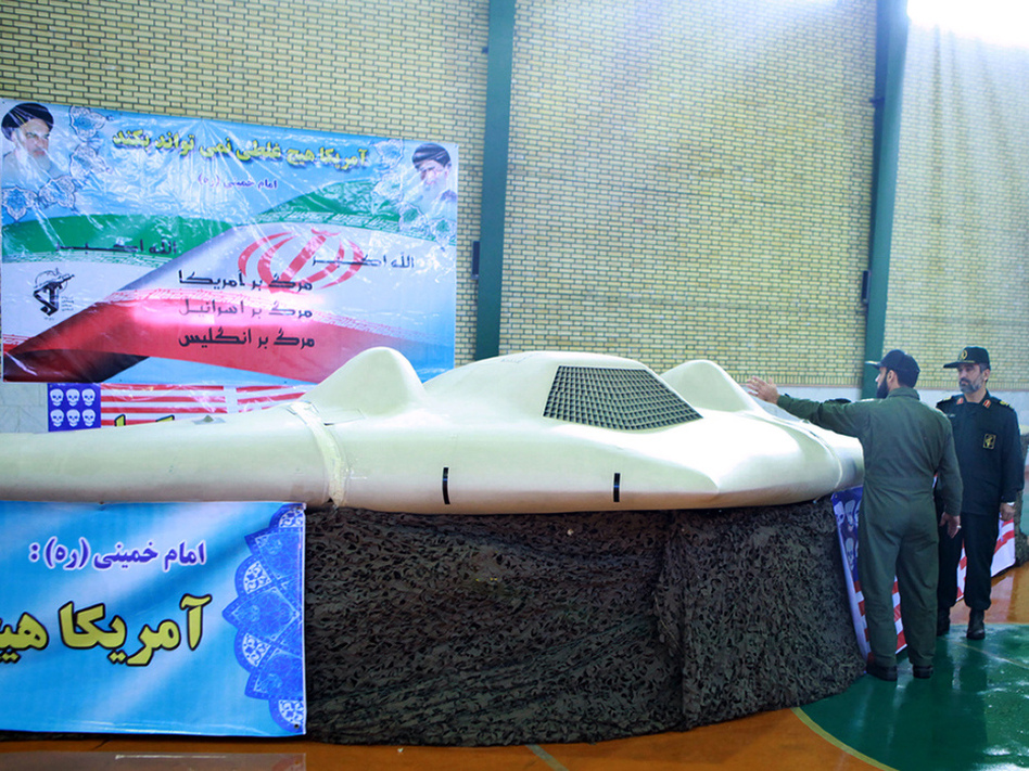 A picture released by the official website of Iran's Revolutionary Guards on December 8, 2011 shows Iranian Revolutionary Guard, Brig. Gen. Amir-Ali Hajizadeh (R) looking at what Iranian officials claim is a U.S. RQ-170 Sentinel high-altitude reconnaissance drone that crashed in Iran on December 4. (AFP/Getty Images)