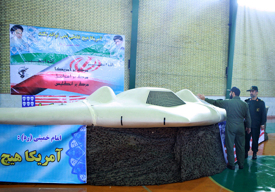A picture released by the official website of Iran's Revolutionary Guards on December 8, 2011 shows Iranian Revolutionary Guard, Brig. Gen. Amir-Ali Hajizadeh (R) looking at what Iranian officials claim is a U.S. RQ-170 Sentinel high-altitude reconnaissance drone that crashed in Iran on December 4.