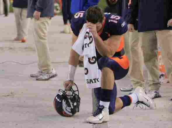 """Denver Broncos quarterback Tim Tebow bows his head on the sidelines — the gesture that's been enshrined as """"tebowing"""" — after scoring a touchdown against the New York Jets on Nov. 17. With Tebow at the helm, the Broncos have won six in a row."""