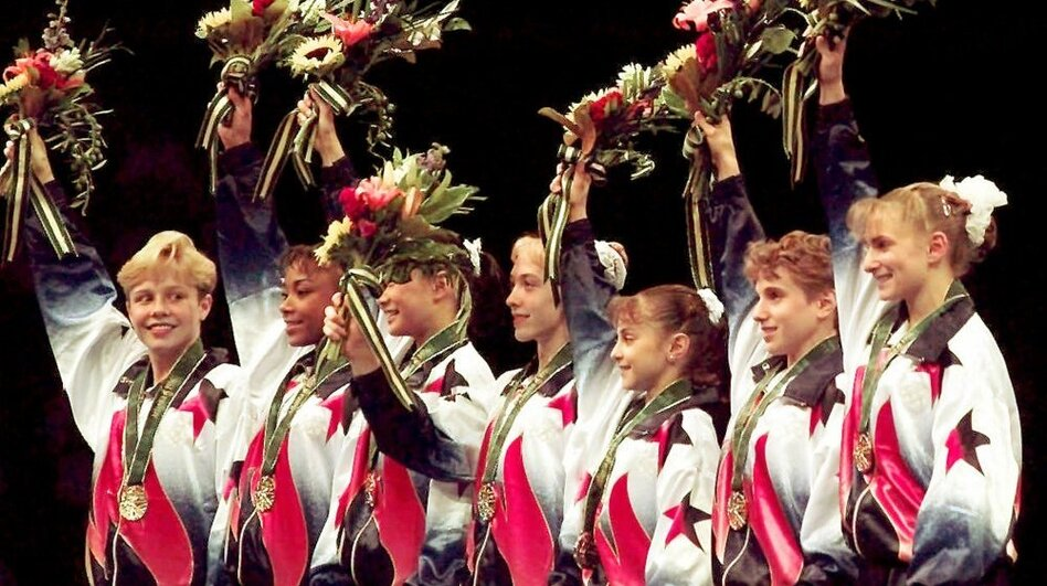 "Dawes and her teammates, known as the ""Magnificent Seven,"" wave to the crowd after being awarded their gold medals in the team competition at the 1996 Summer Games in Atlanta. (AP)"