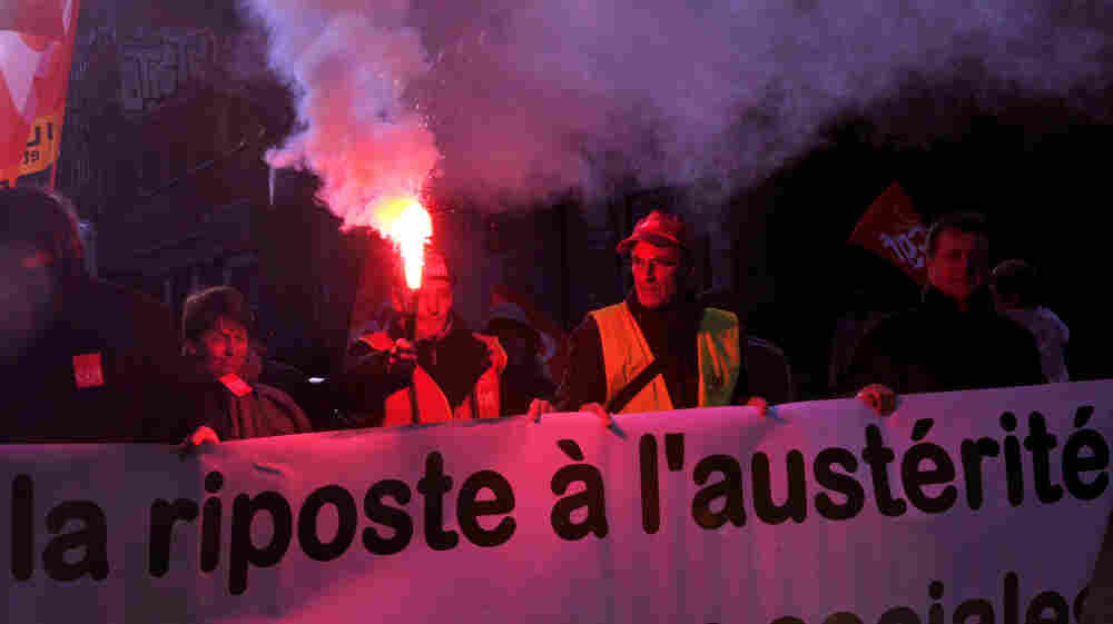 A French man holds a flare during a protest against the government's austerity measures on Tuesday in Lille, northern France. European governments are proposing austerity measures, but critics say there should also be a plan for economic growth.