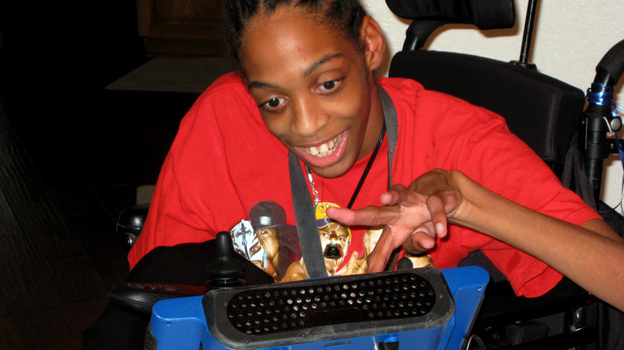 Tres Whitlock types on the DynaVox tablet that serves as his voice. Whitlock, 17, has cerebral palsy and can't speak on his own. He is trying to enroll in a Hillsborough County charter school, but has yet to enroll because of concerns about the therapy and services he needs.  (StateImpact Florida )