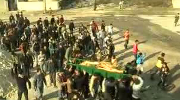 An image grab taken from a video uploaded on YouTube shows Syrian mourners carrying the coffin of a woman who was reportedly killed in the al-Hula region of central Homs province on December 12, 2011.