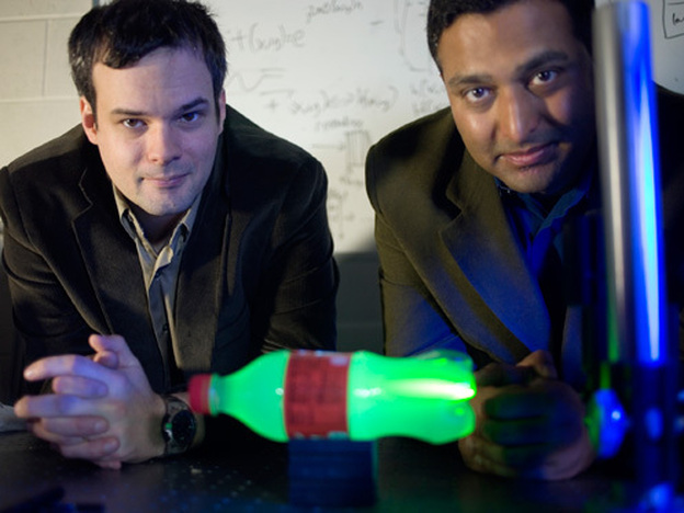 MIT Media Lab postdoc Andreas Velten, left, and Associate Professor Ramesh Raskar. In the foreground is a plastic bottle glowing with laser light. (MIT)