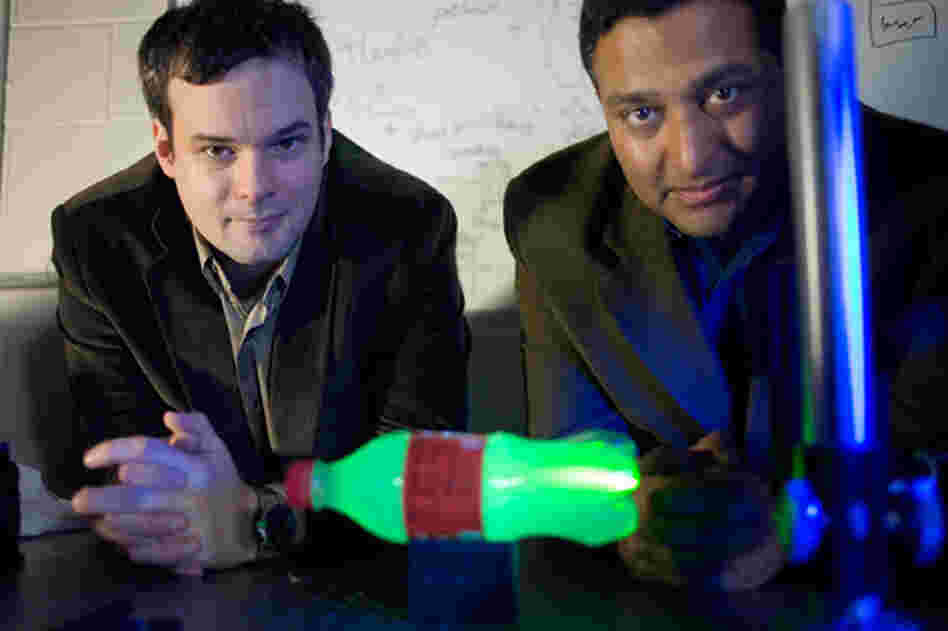 MIT Media Lab postdoc Andreas Velten, left, and Associate Professor Ramesh Raskar. In the foreground is a plastic bottle glowing with laser light.