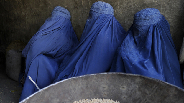 Burqa-clad Afghan women wait to buy chickpeas from a shop in Kabul earlier this year. (AFP/Getty Images)