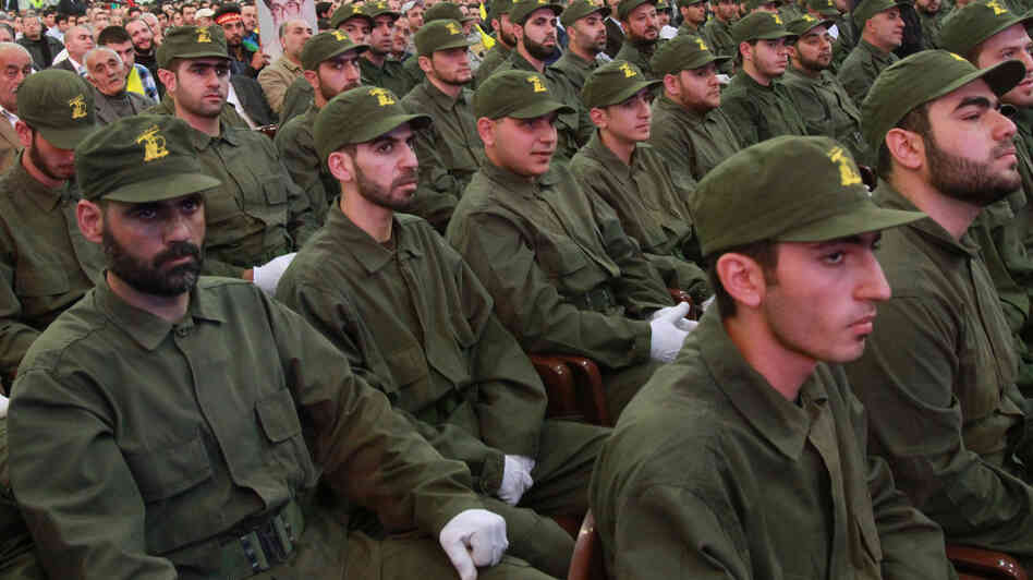 Hezbollah members listen to a speech by the group's l