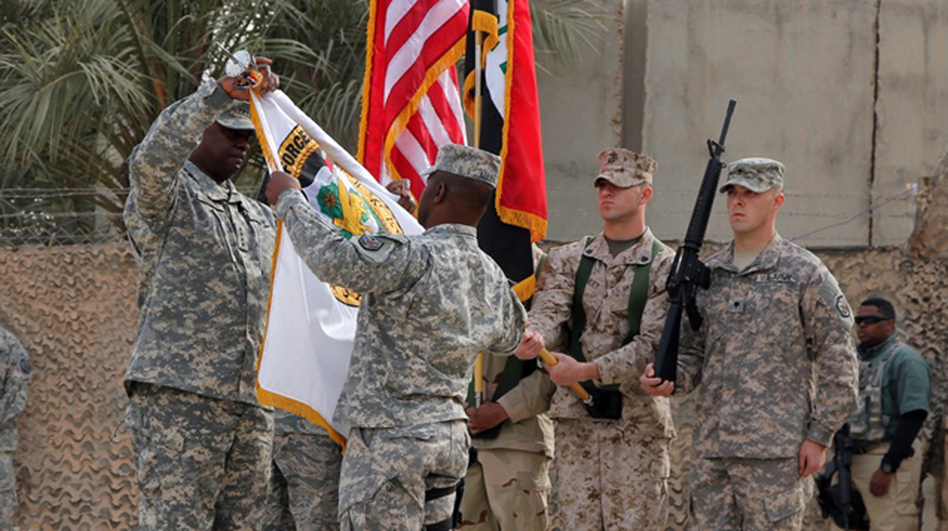 "Gen. Lloyd Austin, the top U.S. commander in Iraq, and Command Sgt. Maj. Joseph Allen ""case the colors"" at the ceremony in Baghdad marking the official end of the U.S. military mission in Iraq."