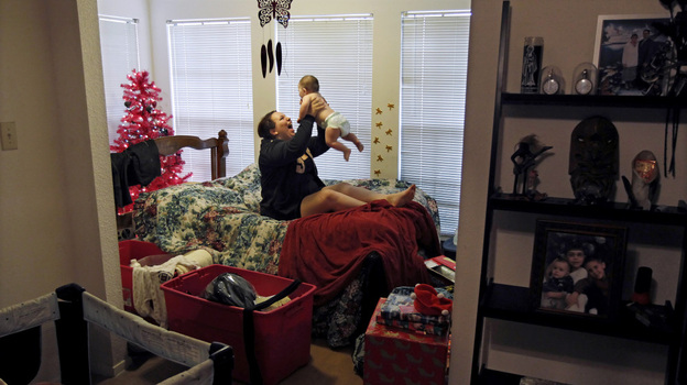 Zenobia Bechtol, 18, and her 7-month-old baby girl, Cassandra, play in the dining room of her mother's Austin, Texas, apartment, where they moved she and her boyfriend were evicted from their apartment.