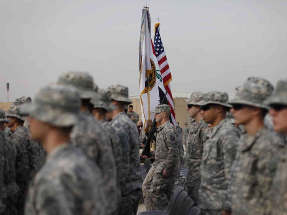 The American flag, Iraqi flag, and the U.S. Forces Iraq colors are carried during ceremonies in Baghdad today marking the end of the U.S. military mission in Iraq.