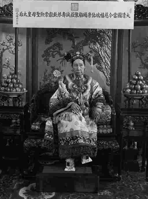 "This photograph is one of a series of photos that shows Cixi seated on her throne in front of a banner that declares her full title. Click here to see a close-up of her ""horse-hoof"" platform shoes."