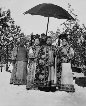 Cixi, accompanied by her attendants, stands in the snowy gardens of Wanshoushan (Longevity Hill), the central hill of the Summer Palace. The image is one of nine similar photographs that were most likely taken for the enjoyment of the empress and her attendants – not for any diplomatic purpose.