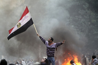 An Egyptian protester waves his national flag while making the victory sign outside the parliament building during clashes with soldiers near Cairo's Tahrir Square on Friday.
