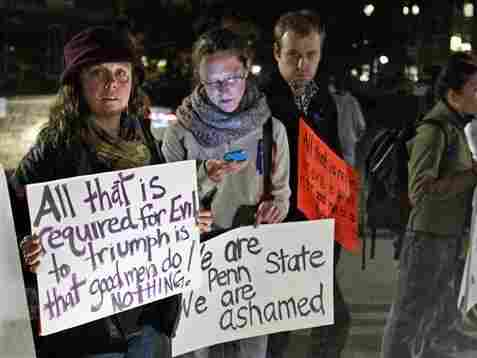 Students stand outside Penn State's Old Main building, protesting the handling of a child abuse scandal involving retired Penn State assistant football coach Jerry Sandusky.