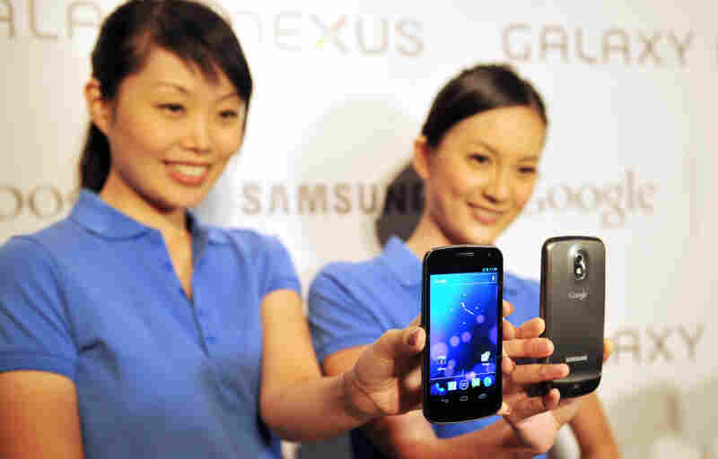 """Models hold the new Samsung Galaxy Nexus Android phone during its official launch in Hong Kong in October. The new smartphone runs Google's Android """"Ice Cream Sandwich"""" operating system."""