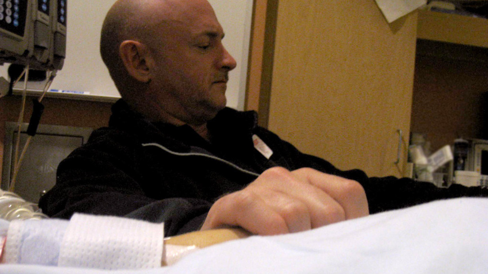 "Mark Kelly holds his wife's hand in her hospital room on Jan. 9 in Tucson, Ariz., the day after she was shot. He has had to make critical choices about her care. ""The key,"" he tells NPR's Neal Conan, ""is knowing what requires a quick decision and what you can put off, and try to gather more information and decide later."""