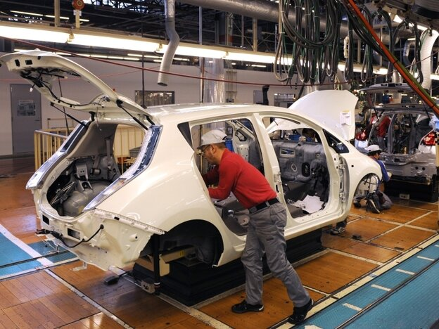 A worker installs components into a Leaf electric vehicle at the company's plant in Kanagawa, Japan.