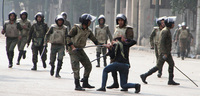 Egyptian army soldiers arrest a woman protester during clashes with military police near Cairo's Tahrir Square.