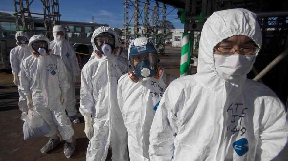 Workers in protective suits and masks wait to enter the emergency operation center at the crippled Fukushima Da