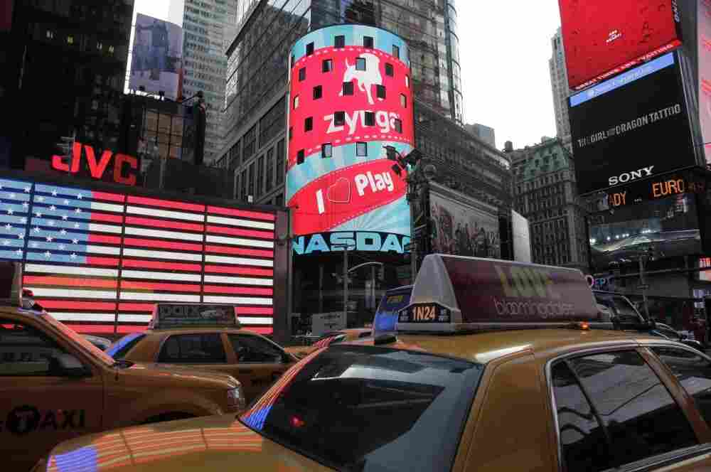 The corporate logo for Zynga, center, is shown on an electronic billboard at the Nasdaq MarketSite on Friday.