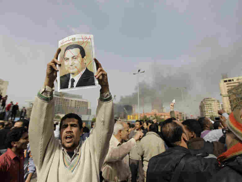 """An Egyptian anti-government protester holds a defaced poster of Egyptian President Hosni Mubarak, with the words """"Mubarak, get out"""" written above, during a demonstration in Cairo in January."""