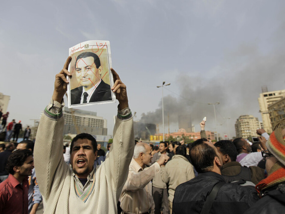 "An Egyptian anti-government protester holds a defaced poster of Egyptian President Hosni Mubarak, with the words ""Mubarak, get out"" written above, during a demonstration in Cairo in January.  (AP)"