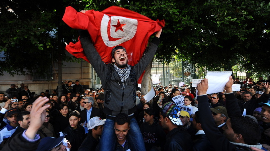 Tunisians protest outside the gates to the French Embassy in Tunis. Arab Spring began in Tunisia when a fruit vendor set himself on fire in protest in front of a government building. (AFP/Getty Images)