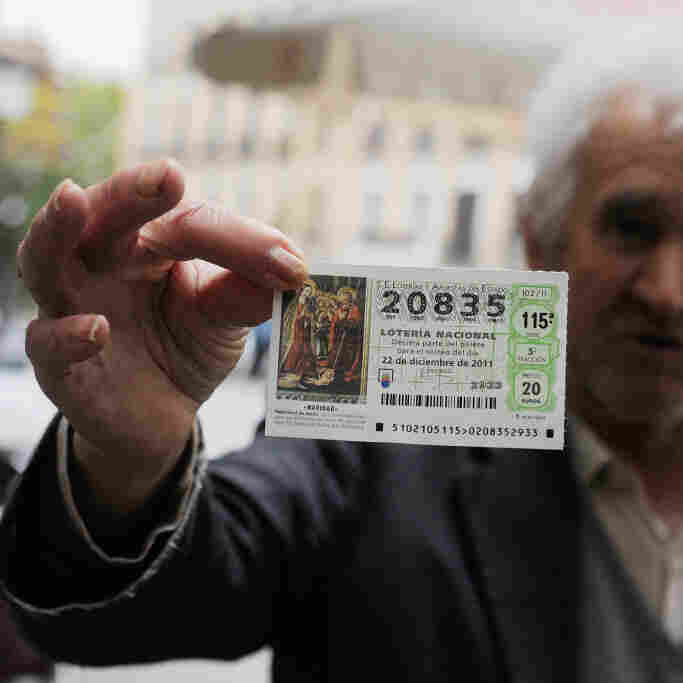A man holds a Christmas 'El Gordo' lottery ticket he is hoping to sell in November in Madrid, Spain. It's a tradition for many people in Spain to buy tickets for the annual lottery, the largest of the year.
