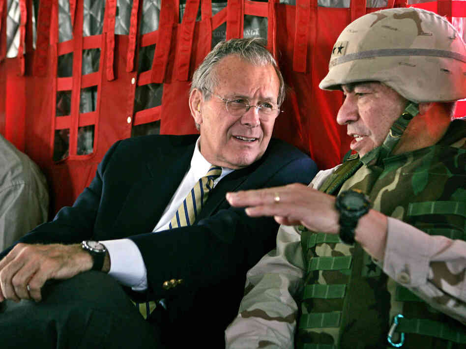 Secretary of Defense Donald Rumsfeld, left, listens to Gen. Ricardo Sanchez, Commander of the coalition forces in Iraq, on a flight from Kuwait City to Baghdad in 2004.