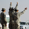 Soldiers wave to the last American military convoy to depart Iraq after it crosses over the border into Kuwait on Sunday.