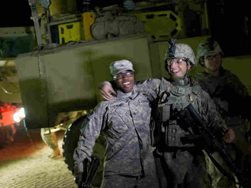 U.S. soldiers celebrate as the first vehicles of the last U.S. military convoy carrying troops out of Iraq passes through the K-Crossing at Iraq's border with Kuwait early on Sunday morning.