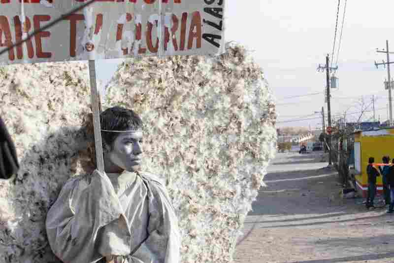 "Young members of the evangelical church Psalm 100 in Ciudad Juarez dress as ""messenger angels"" to silently protest the Mexican city's ongoing violence. Here, 15-year-old Adan Ubacio Lopez holds a sign that translates to ""Behold, I am here, Lord. I will bear your glory."""