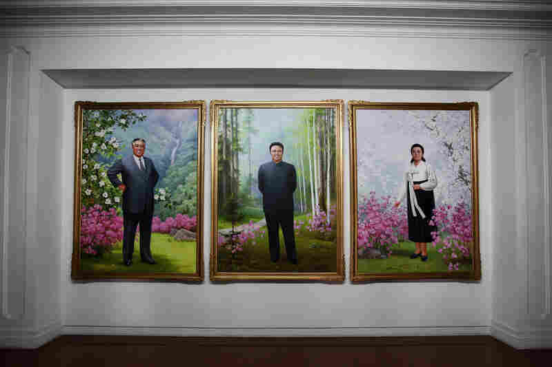 Portraits of Kim Il Sung (left) and Kim Jong Il (center) are seen inside a government building.
