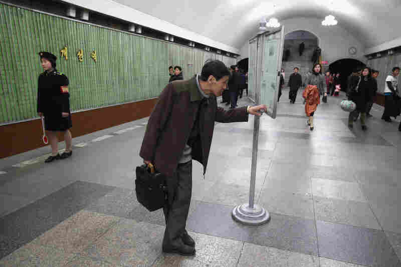 A man reads an official state newspaper on the platform of the Yongwang subway station.