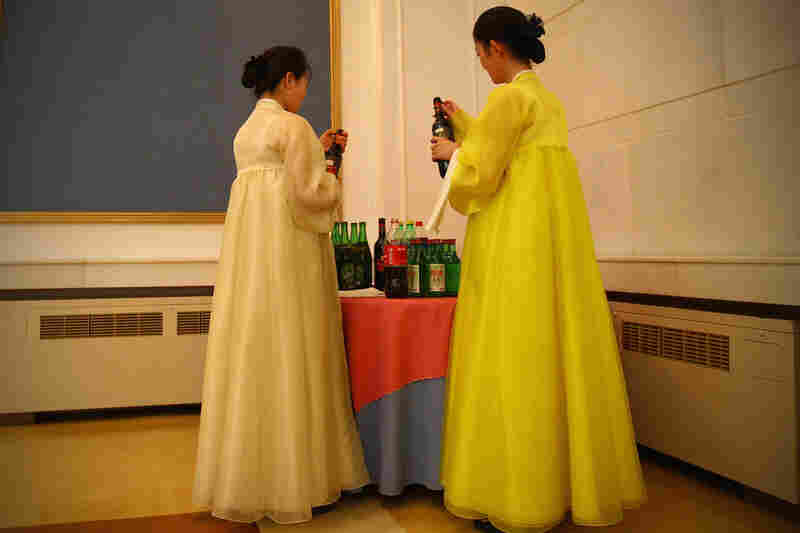 Two North Korean waitresses open bottles of wine during an official reception in the capital, Pyongyang.