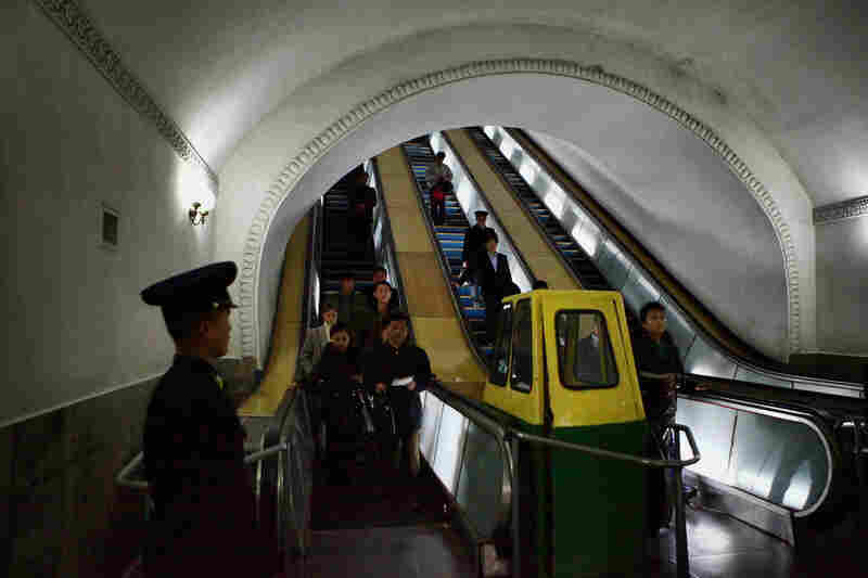 Commuters move by escalator at Puhung Subway station.