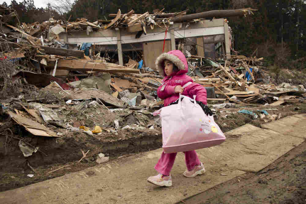 Neena Sasaki, 5, carries some of the family belongings from her home that was destroyed after the earthquake and tsunami in Rikuzentakata, Miyagi province, Japan, March 15.