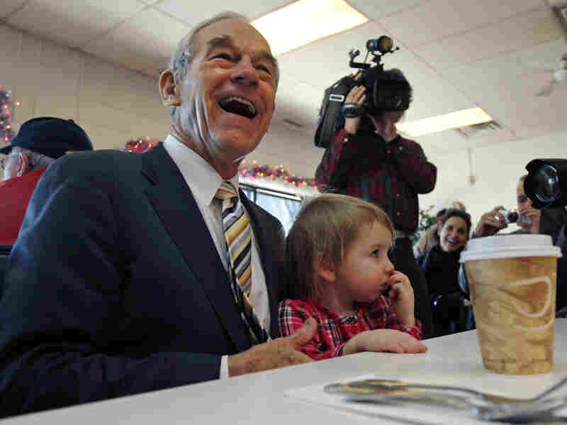 Republican presidential candidate Ron Paul laughs as he sits down with Elizabeth Rose Chamberlain, 3, of Epping, N.H., while campaigning at the Early Bird Cafe in Plaistow, N.H., on Tuesday.
