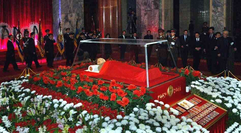 The body of North Korean leader Kim Jong Il is seen as people pay their respects in Pyongyang on Dec. 20. South Korean analysts say power in the North is likely to be vested in a new leadership group, with Ki